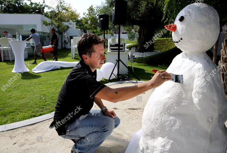 Ben Elliott-Scott Ben Elliott-Scott of Desert Snow company, a company which specializes in artificial snow, works on a snowman, a few hours ahead of a Christmas party at a private villa, in Dubai, United Arab Emirates. The Middle East's brashest city is increasingly embracing the trappings of Christmas in a way that would be unthinkable in more conservative parts of the Muslim world. Christmas trees adorn shopping centers and residential neighborhoods, and high-end hotels try to outdo one another with extravagant and boozy holiday dinners