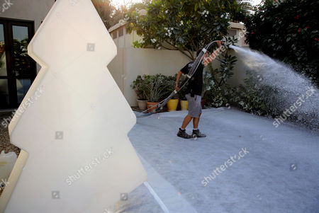 Ben Elliott-Scott Ben Elliott-Scott of Desert Snow company, a company which specializes in artificial snow, blasts trees with manmade flurries to turn them wintery white, a few hours ahead of a Christmas party at a private villa, in Dubai, United Arab Emirates. The Middle East's brashest city is increasingly embracing the trappings of Christmas in a way that would be unthinkable in more conservative parts of the Muslim world. Christmas trees adorn shopping centers and residential neighborhoods, and high-end hotels try to outdo one another with extravagant and boozy holiday dinners