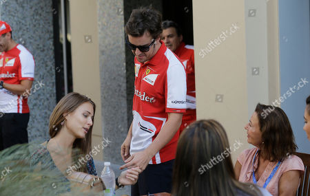 Stock Image of Ferrari driver Fernando Alonso of Spain, right, shares a moment with his girlfriend Russian model Dasha Kapustina, prior to the start of the qualifying session at the Yas Marina racetrack in Abu Dhabi, United Arab Emirates, . At right is Fernando Alonso mother Ana Diaz