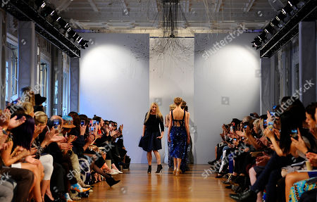 Australian fashion designer Collette Dinnigan, center left, acknowledges applauses after the presentation of her ready-to-wear Spring/Summer 2014 fashion collection, in Paris, Monday, Sept.30, 2013
