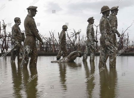 One of seven statues of the team of U.S. General Douglas MacArthur reeanacting his historic landing is toppled as it was hit by strong winds during Typhoon Haiyan in Tacloban city, Leyte province, central Philippines on . Four days after Typhoon Haiyan struck the eastern Philippines, assistance is only just beginning to arrive. Authorities estimated the storm killed 10,000 or more across a vast swath of the country