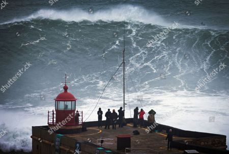 People watch an unidentified surfer ride a big wave at the Praia do Norte, north beach, at the fishing village of Nazare in Portugal's Atlantic coast . On Monday Brazilian suffer Carlos Burle surfed a wave here that surf media suggest could be the biggest wave ever surfed and Maya Gabeira, also from Brazil, nearly drowned and was taken to hospital with a broken ankle after falling in a big wave