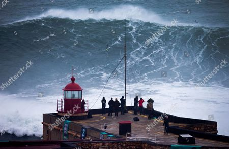 People watch an unidentified surfer ride a big wave at the Praia do Norte, north beach, at the fishing village of Nazare in Portugal's Atlantic coast on . On Monday Brazilian suffer Carlos Burle surfed a wave here that surf media suggest could be the biggest wave ever surfed and Maya Gabeira, also from Brazil, nearly drowned and was taken to hospital with a broken ankle after falling in a big wave