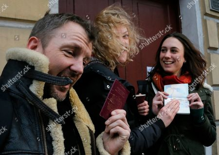 Sini Saarela, Philip Ball, Alexandra Harris Greenpeace International activists, from left: Philip Ball of the United Kingdom, Sini Saarela of Finland and Alexandra Harris of the United Kingdom show their passports with permission to leave Russia to journalists, near the Federal Migration Service in St.Petersburg, Russia, . Russian investigators have dropped charges against all of the 30 crew of a Greenpeace ship, who were accused of hooliganism following a protest outside a Russian oil rig in the Arctic