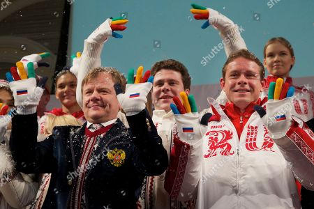 Igor Butman, Pavel Bure, Denis Matsuev From left, jazz musician Igor Butman, pianist Denis Matsuev and former ice hockey star Pavel Bure wave their hands as they present a set of uniforms for the Russian national Olympic team for the upcoming 2014 Winter Olympic Games in Sochi, in Moscow, Russia, . The games will run from Feb. 7 to Feb. 23, 2014