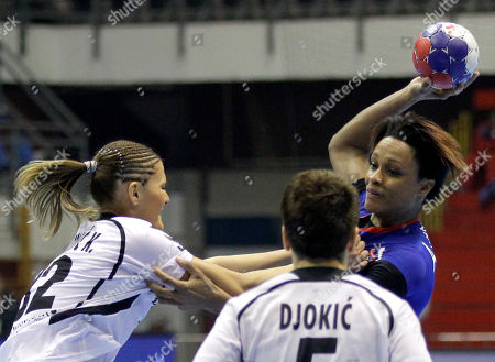 France's Alison Pineau, right, tries to score past Montenegro's Katarina Bulatovic, left, and Ana Djokic during their preliminary round Group A match at Women's Handball World Championship, in Belgrade, Serbia