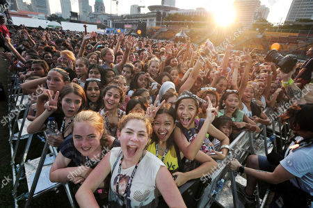 Stock Photo of Fans smile at a photographer as American singer-songwriter Adam Young performs during a closing concert in Singapore, a day after the Singapore Formula One Grand Prix