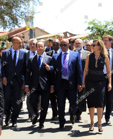 French president Francois Hollande, second from left, walks on the street with companion, Valerie Trierweiler, right, and South Africa's Minister of Justice Jeff Radebe, second from right, to visit the Nelson Mandela National Museum, commonly as the Mandela House in Soweto, South Africa, . Hollande, who is on a two-day state visit to the country, praised South Africa for its efforts to stabilize conflict-prone parts of Africa