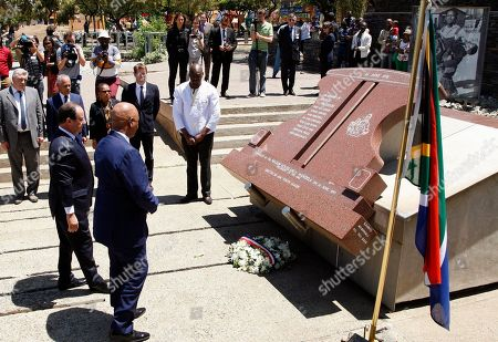 French president Francois Hollande, left, with South Africa's Minister of Justice Jeff Radebe, right, participates in a wreath laying ceremony during their visit to Hector Pieterson Memorial in Soweto, South Africa, . Hollande, who is on a two-day state visit to the country, praised South Africa for its efforts to stabilize conflict-prone parts of Africa. Hector Pieterson became the subject of an iconic image of the 1976 Soweto uprising in South Africa, being carried by another student while his sister ran next to them, was published around the world