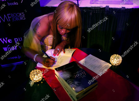 "Zoleka Mandela Author Zoleka Mandela, left, granddaughter of former president Nelson Mandela, signs copies of her book ""When Hope Whispers,"" at it's launch in Johannesburg . The book recounts her struggles with alcohol and drug addiction, losing two of her children and fighting breast cancer"
