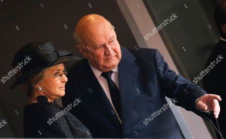 Former South African president FW De Klerk gestures as he arrives with his wife Elita for the memorial service for former South African president Nelson Mandela at the FNB Stadium in Soweto, near Johannesburg, South Africa