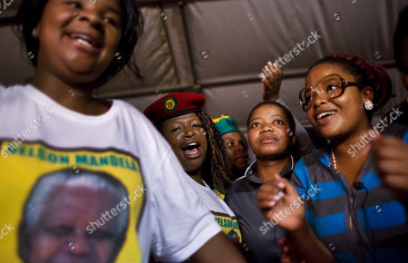 Stock Image of Youth members of the African National Congress (ANC) dance, pray and sing songs honoring Nelson Mandela at a nighttime vigil at the Walter Sisulu University in Mthatha, South Africa, . ANC members, party leaders, and government officials gathered for the traditional night vigil to honor Mandela on the eve of his burial