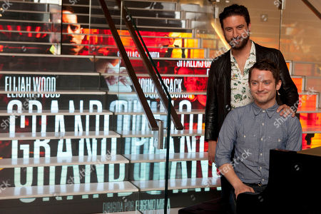 Stock Picture of Eugenio Mira, Elijah Wood Spanish director Eugenio Mira stands next to U.S. actor Elijah Wood sitting in front of the piano attends 'Grand Piano' photocall at the Telefonica Store Gran Via in Madrid, Spain