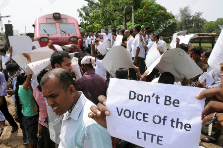 Sri Lankans hold placards while blocking a train carrying Channel 4's British journalist Callum Macrae, in protest against a documentary made by him, in Anuradhapura, Sri Lanka, . The documentary shows soldiers executing naked Tamils and other gruesome footage from the war's 138-day final offensive. Sri Lanka dismissed the video as fake footage and false journalism. Macrae is in Sri Lanka to cover the Commonwealth meeting