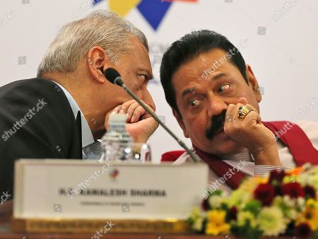 Commonwealth Secretary-General Kamalesh Sharma, left, talks to Sri Lankan President Mahinda Rajapaksa, during a press conference, in Colombo, Sri Lanka, . Rajapaksa on Saturday told reporters that he had already appointed several internal inquiry commissions to investigate the war and reports of missing persons. He also questioned British Prime Minister David Cameron's approach, saying pressure won't do anything to sway Sri Lanka