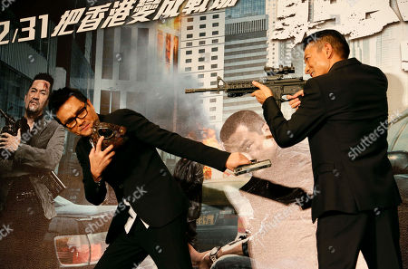 """Gordon Lam, Andy Lau Hong Kong actors Gordon Lam, left, and Andy Lau, pose with props for photographers during a press event for their latest film """"Firestorm"""" in Taipei, Taiwan"""