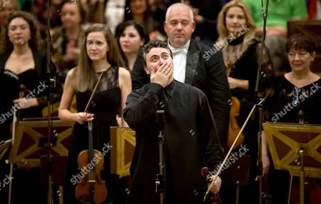 This photo shows Russian-born violinist Maxim Vengerov reacting during a round of applause at the Romanian Athenaeum concert hall in Bucharest, Romania, during the George Enescu classical music festival. The festival which began in 1958 is named after Romanian composer, violinist and conductor George Enescu, who lived in Romania but moved to Paris when the communists came to power