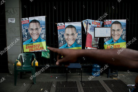 Stock Picture of A man points to an election campaign poster featuring his preferred mayoral candidate, Ernesto Villegas of the ruling party, in Caracas, Venezuela, . Venezuelans will vote in nationwide municipal elections Sunday