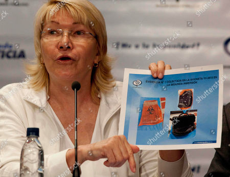 Venezuela's Attorney General Luisa Ortega Diaz holds up an image showing evidence recovered from the small plane YV2615 that crashed in January in the Los Roques islands during a press conference in Caracas, Venezuela, . Venezuelan authorities say navy divers also have recovered five bodies from the plane that was carrying six people, including the CEO of the Italian fashion house Missoni. Attorney General Luisa Ortega told reporters on Monday it would take up to a month to positively identify the remains, which she said were recovered between Oct. 12 and 19. On board when it went down were the 58-year-old Vittorio Missoni, his wife, two Italian friends and the two-man Venezuelan crew