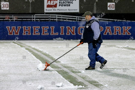 Ronnie Barker of Wheeling, WV, shovels the field at Wheeling Island Stadium in preparation for the West Virginia Class AA Championship football game in Wheeling, WV