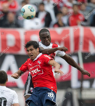 Julian Velazquez, Eder Alvarez Balanta Independiente's Julian Velazquez, front, and River Plate's Eder Alvarez Balanta go for a header during an Argentina's league soccer match in Buenos Aires, Argentina, . River Plate won 2-1 to temporarily take the lead in the tournament with two games left
