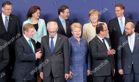Front row, left, to right, Irish Prime Minister Enda Kenny, European Council President Herman Van Rompuy, Lithuanian President Dalia Grybauskaite, French President Francois Hollande and European Parliament President Martin Schultz. Back row left to right, Czech Republic's Prime Minister Petr Necas, Slovenian Prime Minister Alenka Bratusek, Portugal's Prime Minister Pedro Passos Coelho, German Chancellor Angela Merkel and Finland's Prime Minister Jyrki Tapani Katainen speak with each other during a group photo at an EU summit in Brussels on . European Union leaders meet in Brussels ostensibly to agree on ways to find more jobs for the young, who've been disproportionately punished by years of crisis and recession
