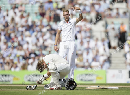 England's Chris Broad at rear, gestures for a trainer as Australia's Shane Watson drops to the ground after being hit by a ball bowled by Broad during play on the first day of the fifth Ashes cricket Test at the Oval cricket ground in London