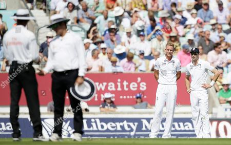 England's Chris Broad, second right and teammate Ian Bell watch the umpires look at the ball as they play Australia during play on the first day of the fifth Ashes cricket Test at the Oval cricket ground in London, . The umpires decided not to change the ball