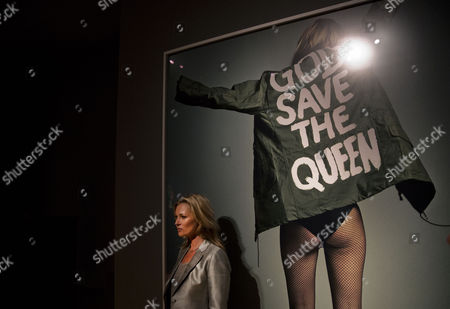 """British model Kate Moss poses for photographers beside an image of her for i-D magazine by Craig McDean at Christie's auction house in London, . The auction """"Kate Moss - From the Collection of Gert Elfering"""" will take place on September 25"""