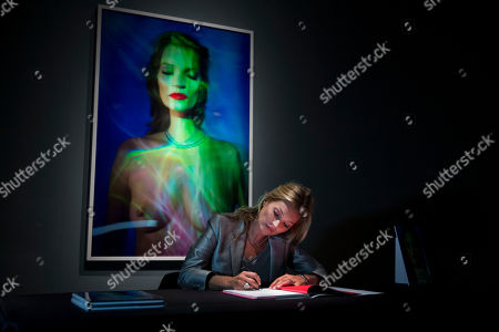 """Stock Image of EDS NOTE NUDITY - British model Kate Moss signs a copy of the auction catalogue as she poses for photographers in front of an image of her for i-D magazine by Craig McDean at Christie's auction house in London, . The auction """"Kate Moss - From the Collection of Gert Elfering"""" will take place on September 25"""
