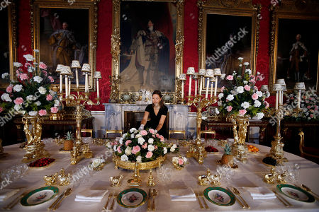 "Caroline de Guitaut, curator of the exhibition "" The Queen's Coronation 1953 "" at the Buckingham Palace in central London, poses for the photographers at a table dressed to evoke the settings of Britain's Queen Elizabeth II's 1953 Coronation State Banquets. This year marks the 60th anniversary of the coronation and to celebrate this anniversary, a special exhibition brings together an array of the dress, uniform and robes worn for the historic event. Paintings, objects and works of art relating to the Coronation will also be on display from July 27 until Sept. 29, 2013"