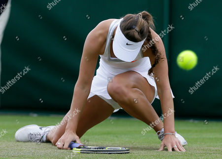 Michelle Larcher De Brito of Portugal slips as she plays Melanie Oudin of the United States during their Women's first round singles match at the All England Lawn Tennis Championships in Wimbledon, London