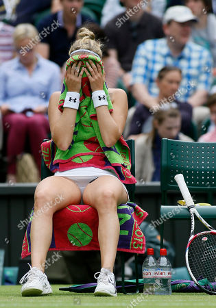 Mathilde Johansson of France covers her face with a towel during a change of ends break as she plays Agnieszka Radwanska of Poland during their Women's second round singles match at the All England Lawn Tennis Championships in Wimbledon, London