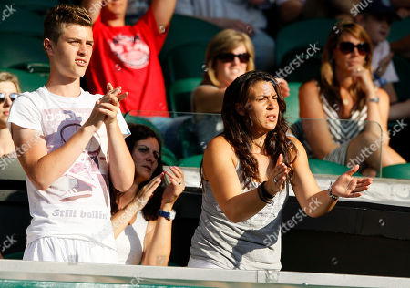 Ladies singles Wimbledon champion Marion Bartoli of France, right, applauds as she watches Bruno Soares of Brazil and Lisa Raymond of the United States play Daniel Nestor of Canada and Kristina Mladenovic of France during the mixed doubles final match at the All England Lawn Tennis Championships in Wimbledon, London