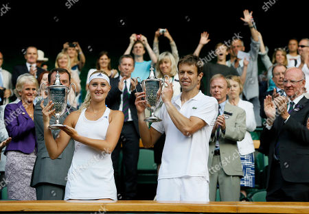 Daniel Nestor of Canada, right, and Kristina Mladenovic of France pose with their trophies after they won against Bruno Soares of Brazil and Lisa Raymond of the United States in the mixed doubles final match at the All England Lawn Tennis Championships in Wimbledon, London