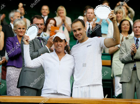 Bruno Soares of Brazil, right, and Lisa Raymond of the United States pose with the trophy for runner up after losing to Daniel Nestor of Canada and Kristina Mladenovic of France after the mixed doubles final match at the All England Lawn Tennis Championships in Wimbledon, London