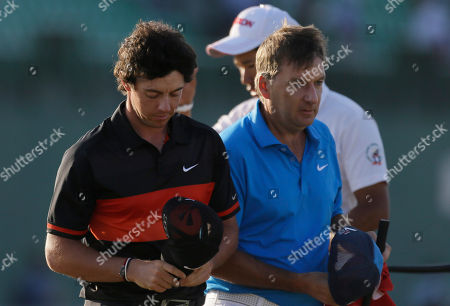 Stock Picture of Rory McIlroy of Northern Ireland and his caddie J. P. Fitzgerald, right, walk off the 18th green after the second round of the British Open Golf Championship at Muirfield, Scotland