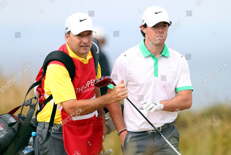 Rory McIlroy of Northern Ireland passes his club to his caddie J. P. Fitzgerald after playing off the 6th tee during the first round of the British Open Golf Championship at Muirfield, Scotland