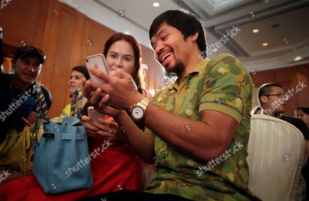 Manny Pacquiao, Jinkee Pacquiao Filipino boxer and Congressman Manny Pacquiao chats with his wife Jinkee, left, prior to a press conference in Shanghai, China, . Pacquiao will fight with Brandon Rios of the United States in a welterweight bout at Venetian Macao on Nov. 24 in Macau