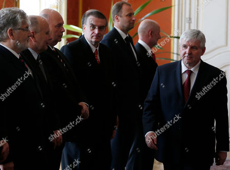 """Czech Republic's Prime Minister Jiri Rusnok, right, walks past newly appointed government members at the Prague Castle in Prague, Czech Republic, . Czech President Milos Zeman has sworn in a new government to replace that of Petr Necas who was forced to resign over a spy and bribery scandal. The government, led by Zeman's economy adviser Jiri Rusnok, consists mostly of the president's allies, including a sponsor of his presidential campaign and an unsuccessful presidential candidate who later supported Zeman's presidential bid. Zeman has called it a government of """"experts"""" and Rusnok said it is a priority for it to prepare the 2014 state budget"""