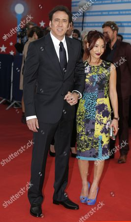 """Actor Nicolas Cage and his wife Alice Kim arrive for the screening of their film """"Joe"""" at the 39th American Film Festival, in Deauville, Normandy, western France"""