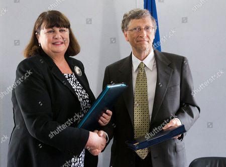 Microsoft founder and philanthropist Bill Gates, right, shake hands with and European Commissioner for Research and Innovation Maire Geoghegan-Quinn after they signed an medical agreement for research support of the Global Fund to fight Tuberculosis and Malaria at the conclusion of their meeting, in Paris