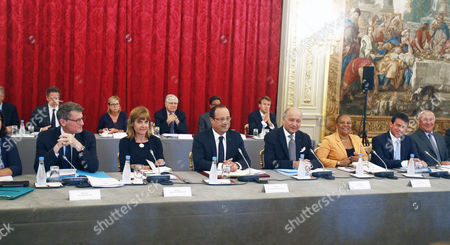 French President Francois Hollande, center, attends a government seminar at the Elysee Palace in Paris, . From left: education minister Vincent Peillon, businesswoman Anne Lauvergeon, Francois Hollande, foreign minister Laurent Fabius, justice minister Christiane Taubira, interior minister Manuel Valls, and employment minister Michel Sapin