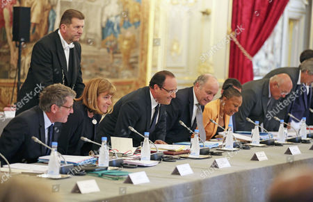French President Francois Hollande, center, and government members, sit, at the start of a government seminar held at the Elysee Palace in Paris, . From left: education minister Vincent Peillon, businesswoman Anne Lauvergeon, Francois Hollande, foreign minister Laurent Fabius, justice minister Christiane Taubira and employment minister Michel Sapin
