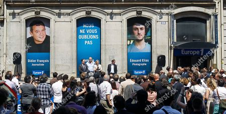 Stock Photo of Florence Aubenas, holding a microphone at center, a French journalist who was held hostage in Iraq, delivers her speech during a gathering for Europe-1 radio reporter Didier Francois and independent photographer Edouard Elias, pictured in banners, who have been missing in Syria since June 6. It's unclear where they are or who is holding them. The meeting was held in front of Europe I radio headquarters in Paris, . Caption at centre reads as 'We will not forget you