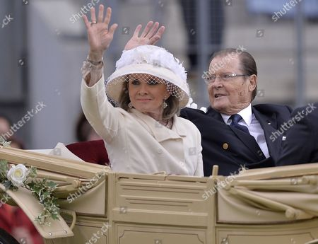 Sir Roger Moore and his wife Kristina Tholstrup riding in a carriage during the opening ceremony of the CHIO Equestrian Festival in Aachen, Germany