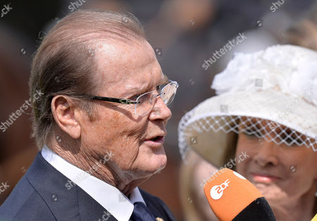 Sir Roger Moore gives an interview, watched by his wife Kristina Tholstrup, right, at the CHIO Equestrian Festival in Aachen, Germany