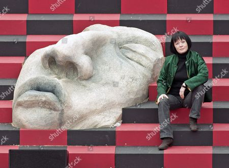 Stock Image of Hsiu-Chin Tsai Stage designer Hsiu-Chin Tsai of Taiwan, poses for photographers besides a giant mask during a press preview in the stage construction for the opera 'Turandot' by Giacomo Puccini at the DomStufen open air festival (Domstufen-Festspiele) in front of the Mariendom (Cathedral of Mary) in Erfurt, central Germany, . The 70 cathedral steps which run between the magnificent architectural ensemble of the Cathedral of St. Mary and the Church of St. Severus are transformed in one of the world´s most beautiful festival stages. The premiere of the opera is on Thursday, July 4, 2013