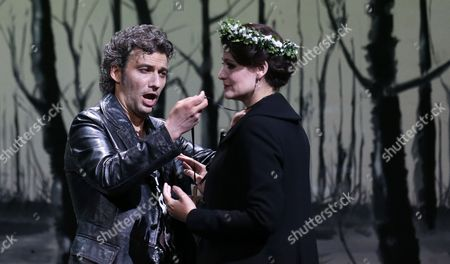 "Jonas Kaufmann, Anja Harteros In this picture taken, Jonas Kaufmann, left, in the role of Manrico and Anja Harteros as Leonora sing during a dress rehearsal for the opera ""Il Trovatore"" by Giuseppe Verdi in the Bavarian State Opera House in Munich, southern Germany. This wild new production by Olivier Py opened the company's annual Munich Opera Festival. It's a non-stop barrage of nightmarish images mixing styles and periods that assault the audience at lightning speed on a multi-tiered revolving set"