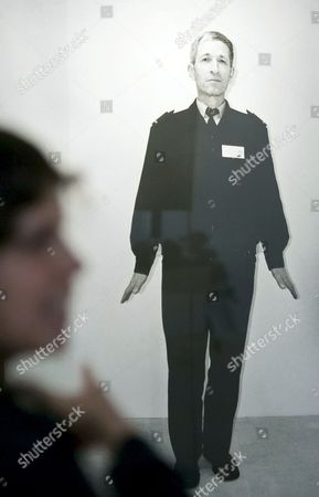 Stock Image of A woman stand in front of the photograph 'Guard' (2009) during a press preview at the exhibition 'Compossibilities' of Russian artist Olga Chernysheva in the Kunsthalle (Art Hall) in Erfurt, central Germany, . In cooperation with the V-A-C Foundation Moscow, the Kunsthalle Erfurt is presenting the first major solo exhibition of Olga Chernysheva's works in Germany. In addition to aquarelles, drawings and paintings from recent years, the exhibition also includes photos and numerous videos, as well as several new works. The exhibition starts on July 4, 2013 and last until Aug. 25, 2013